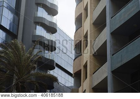 Concrete Facade With Balconies Contrasting With A Glass Facade Building