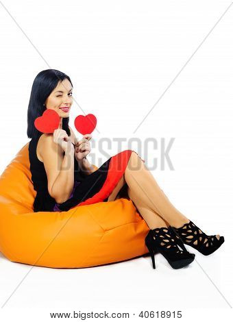 Beautiful Young Brunette Sitting On Couch With Red Valentine Hearts