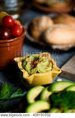 closeup of a ceramic bowl with guacamole, next some slices of avocado in a plate and some cherry tomatoes in an earthenware bowl on a gray rustic wooden table, with some bread buns in the background
