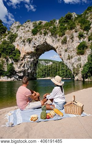 Couple Men And Woman Picnic On The Beach Of The The Famous Natural Bridge Of Pont Darc In Ardeche De