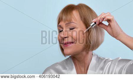 Anti-aging Cosmetics Concept. Beautiful Mature Woman Applying Regenerating Facial Serum Onto Her Ski