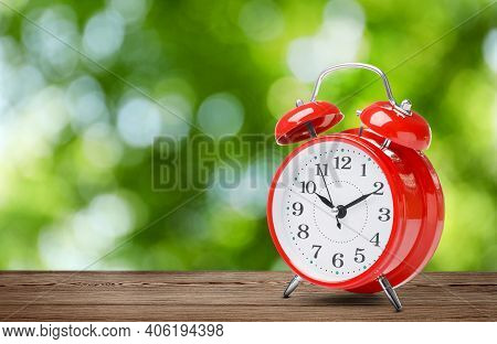 Red Alarm Clock On Wooden Table, Space For Text. Daylight Saving Time (spring Forward)