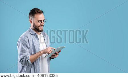 Smart Millennial Guy In Glasses Using Tablet Computer Over Blue Studio Background, Banner Design Wit