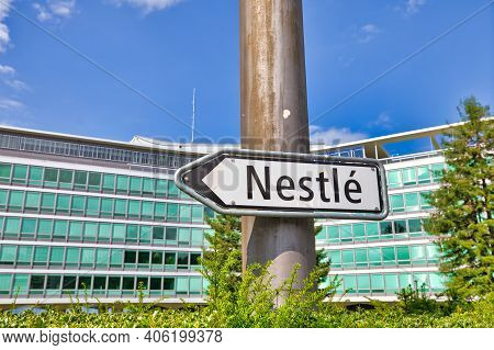 Vevey, Switzerland - August 14, 2020: Sign Indicating Nestle In Foreground And Nestle Hq Building On