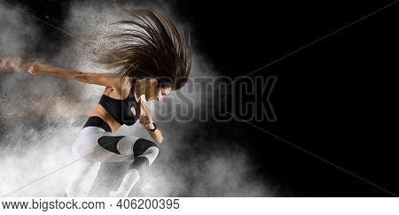 Woman sprinter leaving starting. On smoke background