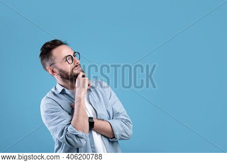 Pensive Caucasian Guy Thinking Over Decision Or Problem, Looking At Empty Space Over Blue Studio Bac