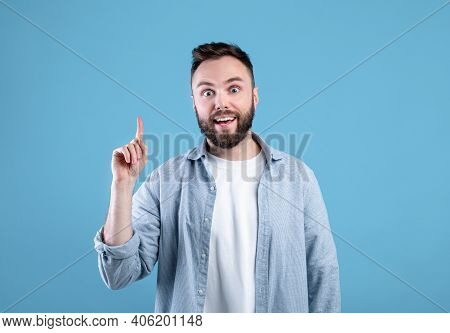 Creativity, Idea, Inspiration. Young Handsome Guy Pointing Finger Up, Gesturing Eureka, Experiencing