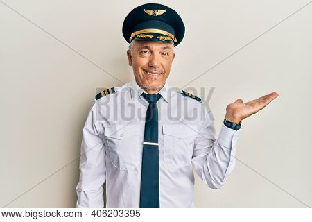 Handsome middle age mature man wearing airplane pilot uniform smiling cheerful presenting and pointing with palm of hand looking at the camera.