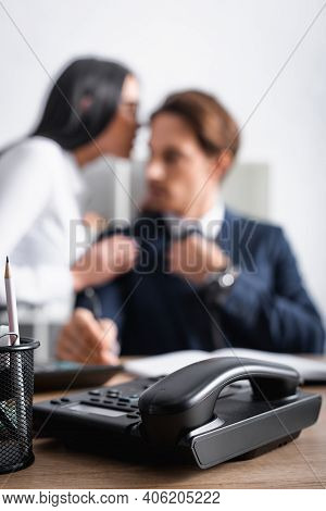 Selective Focus Of Landline Phone Near Businesswoman Flirting With Colleague In Office On Blurred Ba