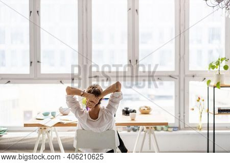 Rear view of young woman working on laptop in loft office