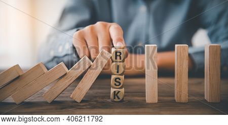 Close-up Hand The Hand Of A Businessman Who Is Stopping Or Preventing A Falling Block.risk Protectio