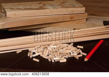 Wooden Pegs Cut From Wooden Sticks On The Table. Carpenter Workshop And Details Of His Woodwork.