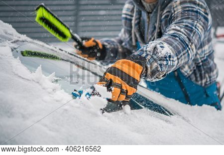 Caucasian Driver Removing Snow And Ice From His Car Windshield. Extreme Winter Season Weather And Th