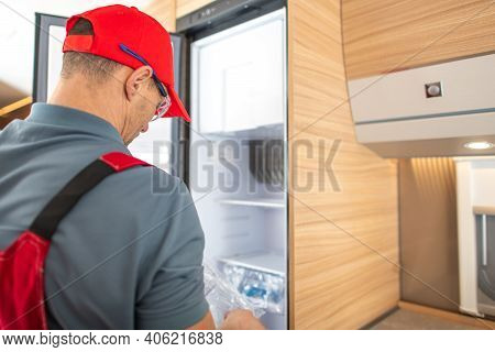 Recreational Vehicle Rv Technician In His 40s Replacing Camper Or Travel Trailer Refrigerator. Rv In