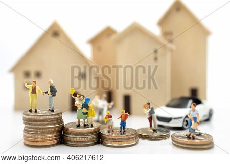 Miniature People: Elderly Person And Family Standing On Coins Stack With Home, Retirement Planning C
