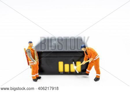 Miniature Worker Digging On Battery. Concept Of Search For Renewable Energy Or New Energy.