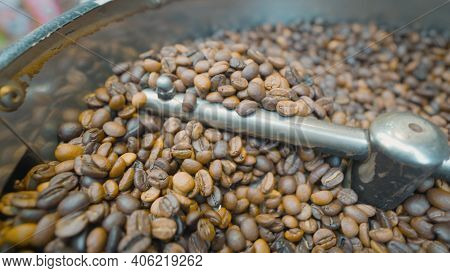 Close-up Of Coffee Beans Stirred And Roasted. Action. Special Machine Mixes Coffee Beans For Thermal