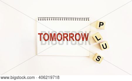 Notepad On A White Background With The Writing Of The Text Tomorrow, Wooden Cubes With The Word Plus