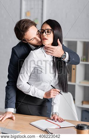 Businessman Seducing Sexy Brunette Secretary Standing With Pen At Workplace.