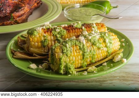Peruvian Elote Street Corn Topped With Queso Fresco Cheese And Aji Verde Spicy Green Sauce