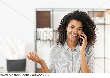 Smiley African American Teenage Girl With Curly Hair Talking On Mobile Phone, Chatting With Friend O