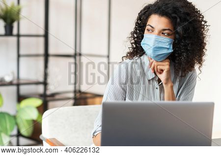 Thoughtful Young African American Female Office Worker With Curly Hair In Protective Face Mask Sitti