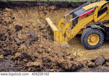 Loader Excavator With Backhoe Planning And Cutting Clay Ground At Eathmoving Works In Construction S