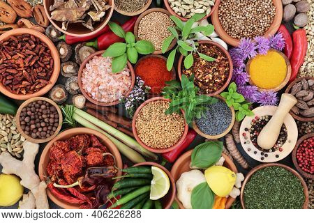Herb and spice assortment in bowls forming a colourful abstract background. Flat lay, top view.