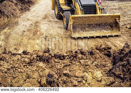 Loader Excavator With Backhoe For Earthmoving Works In Construction Site Pit. Front View. Right-hand