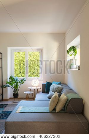 Close up of modern living room with design sofa and colorful pillows above. Bright window with views on garden and decorative plants. Nobody inside