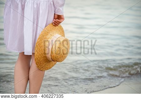 Straw Hat In Female Hand On Seashore At Sunset. Unrecognizable Woman In White Beach Dress Having Res