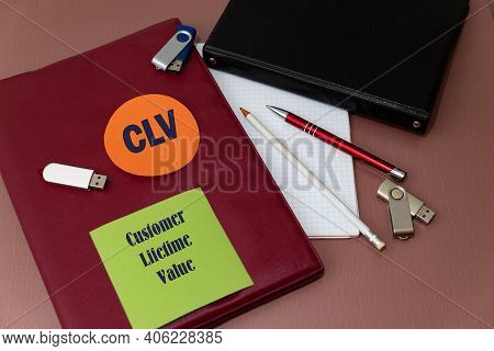 Clv - Customer Lifetime Value Acronym On Colored Stickers. Work Table With Notebooks For Writing, Me