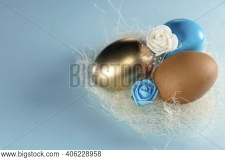 Gold, Blue And Brown Eggs In The Nest. Tree Aggs In Nest. Happy Easter Concept. Painted Eggs In A Ne