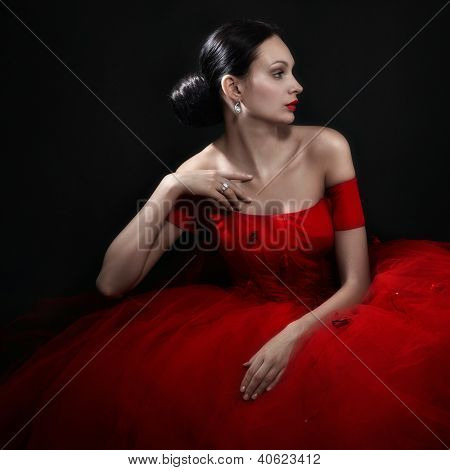 beautiful woman in red evening dress on black
