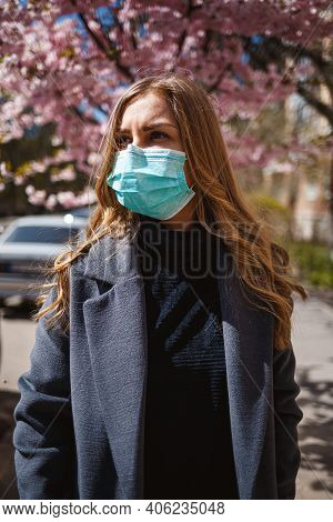 Girl, Young Woman In A Protective Sterile Medical Mask On Her Face, Looking At The Camera Outdoors,