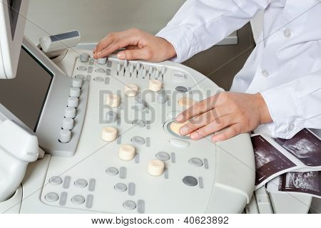 Close up of female radiologist operating ultrasonic machine with sonography print on keypad