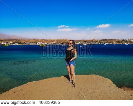 Young Pretty Woman Stands On A Rock Against The Background Of Sharm El-maya Bay In Sharm El Sheikh (