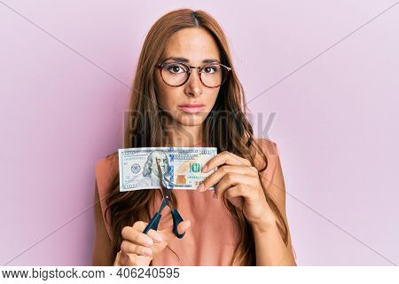 Young brunette woman cutting dollars with scissors for currency devaluation relaxed with serious expression on face. simple and natural looking at the camera.