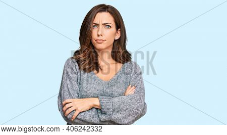 Young brunette woman wearing casual winter sweater skeptic and nervous, disapproving expression on face with crossed arms. negative person.