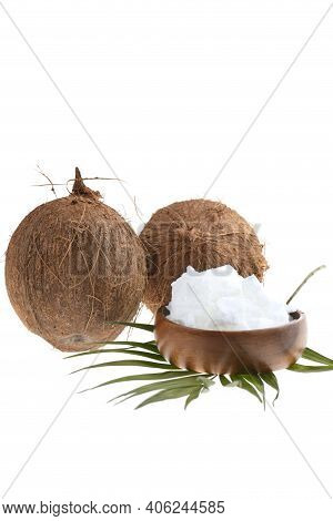 Coconut Organic Pure Oil. Coconut Oil In A Wooden Cup And Coconuts Fruits Close-up With Palm Leaf Is