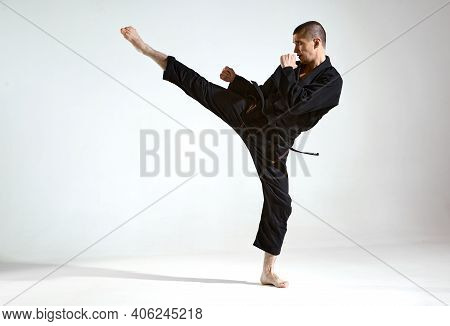 Fighting Guy In Black Kimono Fighter Shows Kudo Technique On Studio Background With Copy Space, Mix