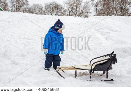 Boy Stands Next To His Sleigh In The Snow