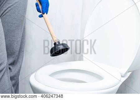 Cleaning Toilet Stuck With Suction Cup. Hands In Gloves Holding Ventuz In Toilet.