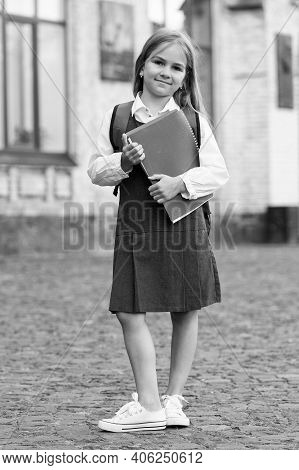 Happy Little Child In School Uniform Hold Library Books In Schoolyard Outdoors, Knowledge Day.