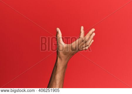 Hand of hispanic man over red isolated background picking and taking invisible thing, holding object with fingers showing space