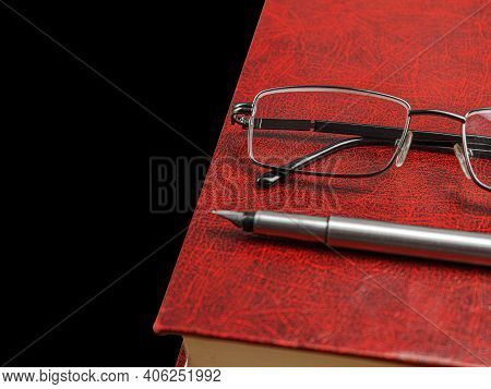 Book With Glasses On A Yellow Background. Finished Book. Closed Red And Expensive Book