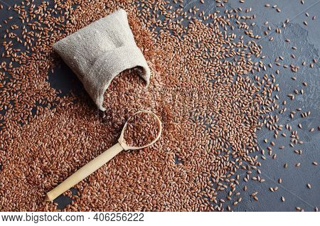 Flax Seeds In Wooden Spoon And Linen Bag.