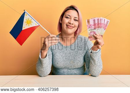 Hispanic woman with pink hair holding philippine flag and philippines pesos banknotes smiling with a happy and cool smile on face. showing teeth.