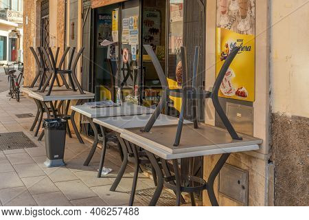 Campos, Spain; January 2021: Brown Plastic Chairs Stacked Next To Outdoor Tables. Restaurant Closed