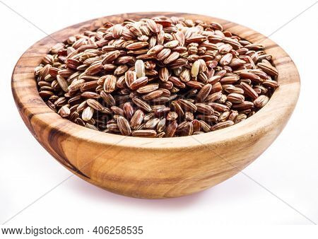 Brown rice - whole grain rice with outer hull or husk in wooden bowl on white background.